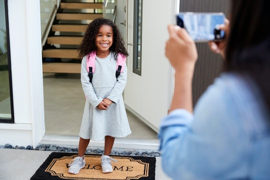 mom taking photo of her child on the first day of school