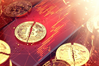 Broken bitcoin split in two pieces laying on a red charts displayed on-screen. Low revenues of crypt...