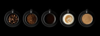 Five black cups with coffee and saucers on black background. Coffee beans, ground coffee, espresso, ...