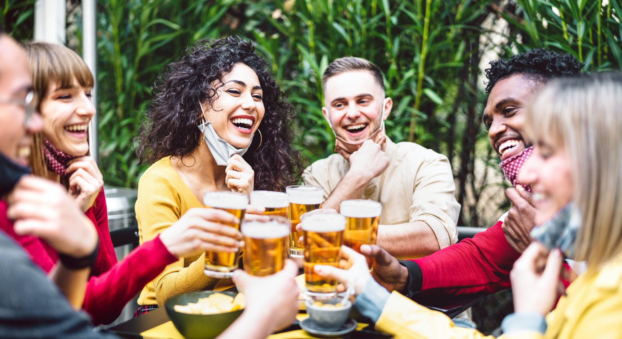 Young people toasting beer wearing open face mask - New normal life style concept with friends havin...