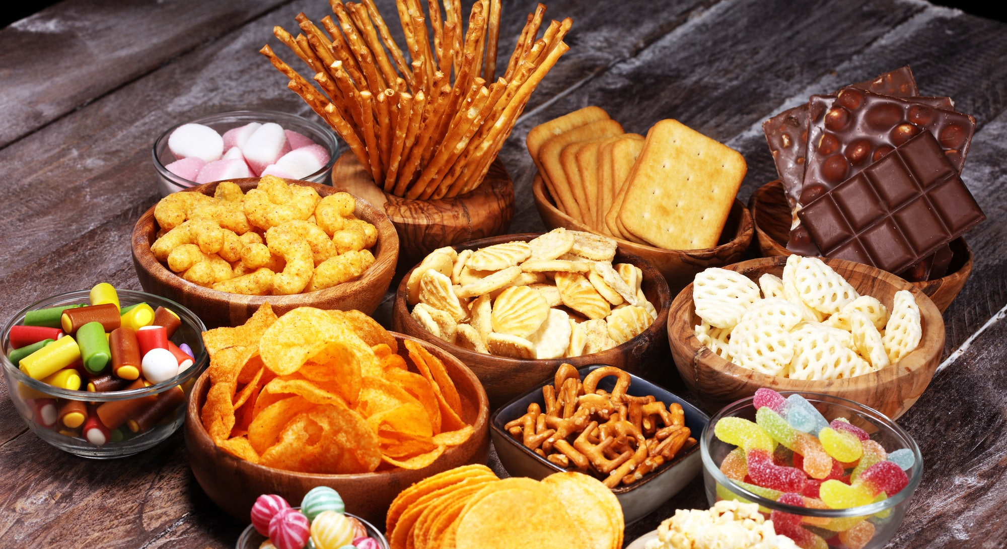 Salty snacks. Pretzels, chips, crackers in wooden bowls. Unhealthy products. food bad for figure, sk...