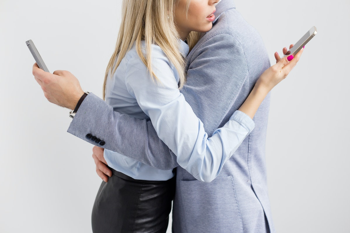 Young couple embrace while keeping busy with their mobile phones