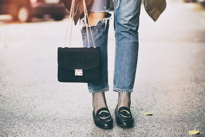 fall fashion outfit details. fashionable woman wearing ripped jeans with loafers, fishnet stockings,...