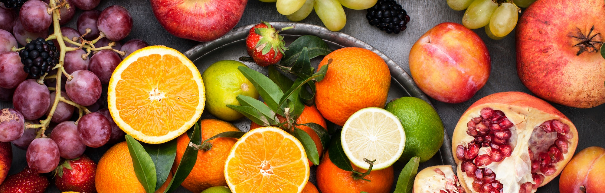 Assorted fruits. Different fruits on a gray background, the whole surface is covered with citrus fru...