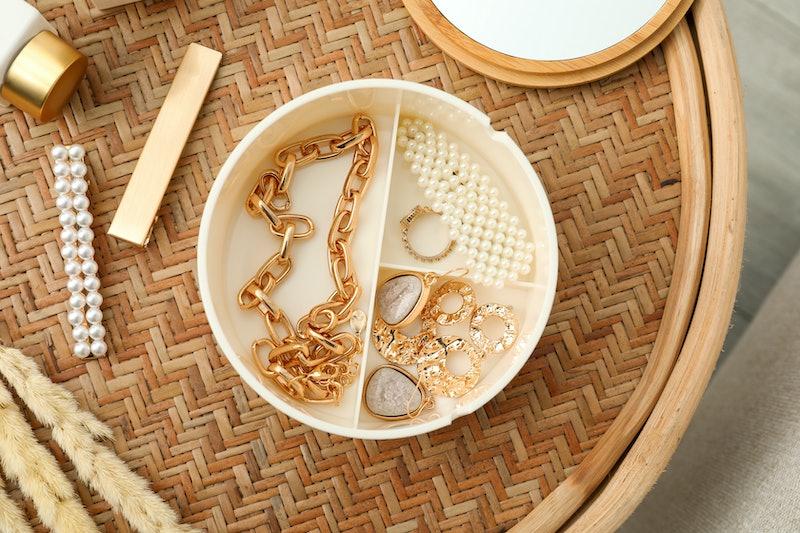 Stylish golden bijouterie on wicker table, top view