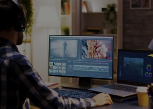 Film maker pointing at the monitor in home office while working on post production for a movie. Vide...