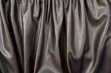 Close up on crumpled black leather material textured fabric. Shiny black pleather as a background.