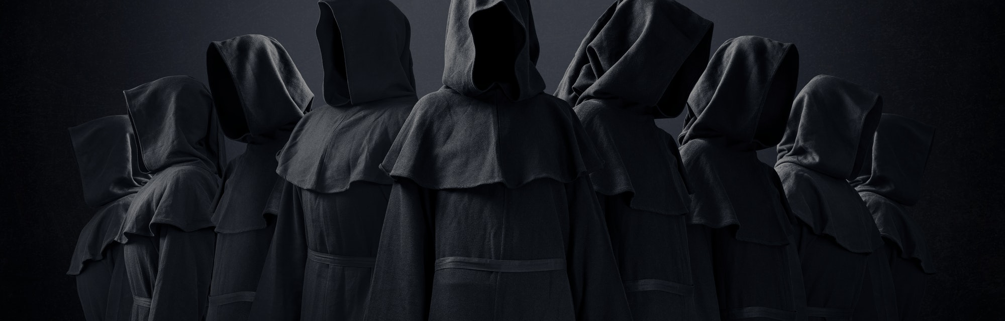 Group of nine scary figures in hooded cloaks in the dark