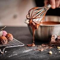 Baker or chocolatier preparing chocolate bonbons whisking the melted chocolate with a whisk dripping...