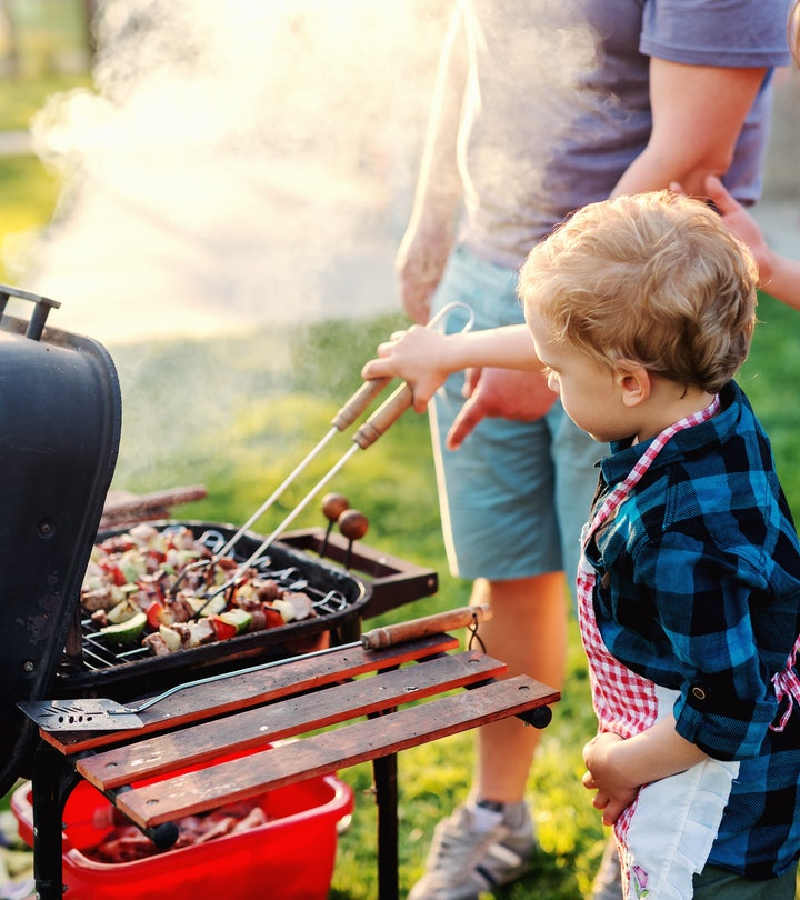 child grilling with father standing nearby for Labor Day