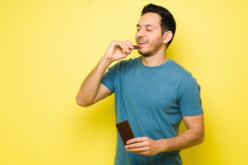 Attractive latin man eating a big chocolate candy bar. Handsome man in his 30s with sugar cravings e...