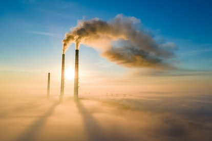 Aerial view of coal power plant high pipes with black smoke moving up polluting atmosphere at sunset...