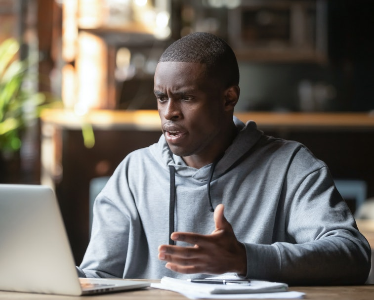 Frustrated black male student work at laptop get mad having device software operational problems, an...