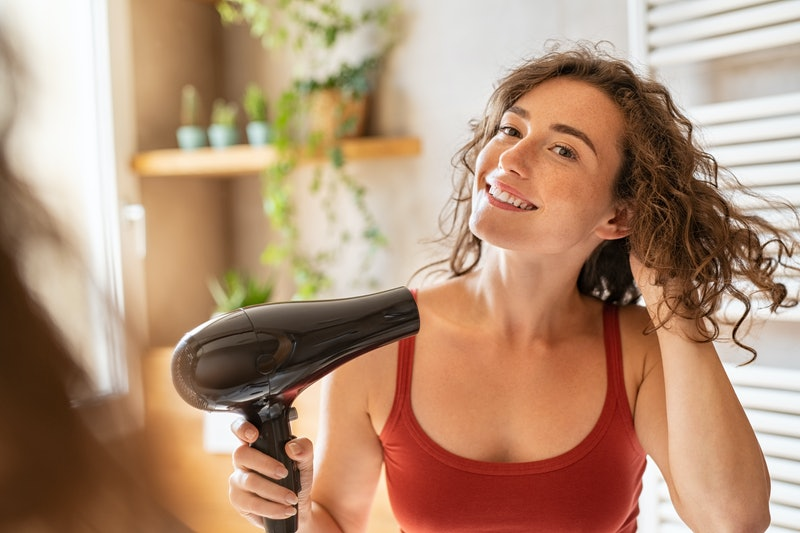 Beautiful girl using a hair dryer and smiling. Natural young woman drying curly hair with hair-dry m...