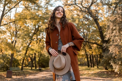 Woman holding hat and sunglasses walking in park dressed in warm coat on the 2021 fall equinox, whic...