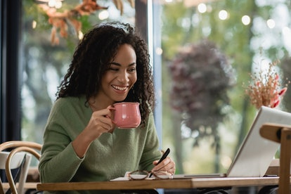 happy african american woman holding pen and cup of coffee while looking at laptop