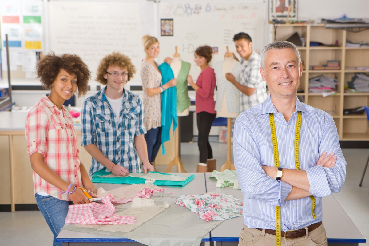 A medium shot of a teacher and young students smiling at camera in a home economics class.