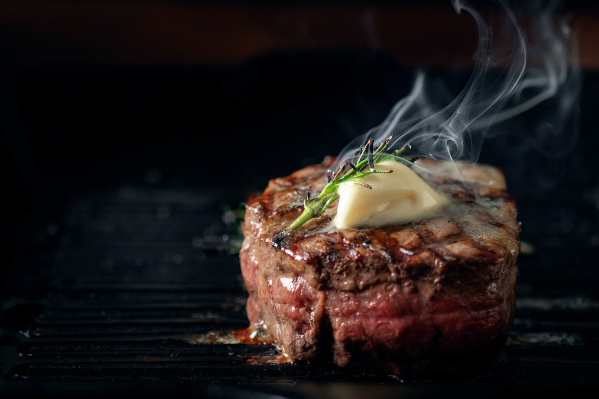 A steaming beef tenderloin steak is grilled in a grill pan with the text copy space. The concept of ...