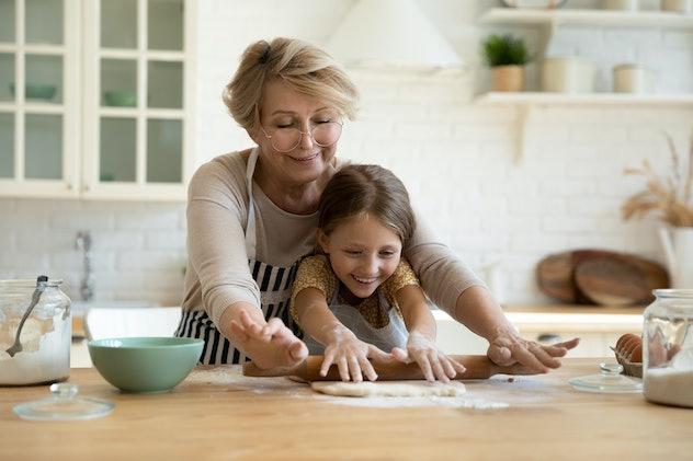 girl helping her grandma roll dough