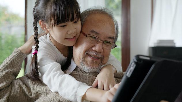 grandpa and granddaughter looking at computer