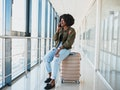Portrait of happy young african american woman sitting on suitcase and talking with mobile phone at ...