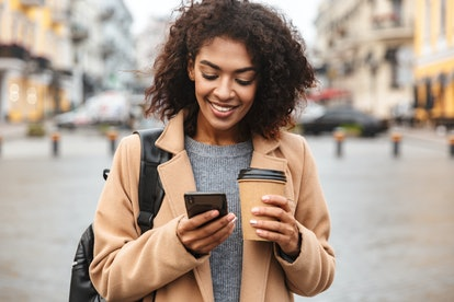 Young woman smiling while having coffee and reading her October 2021 monthly horoscope on her phone.
