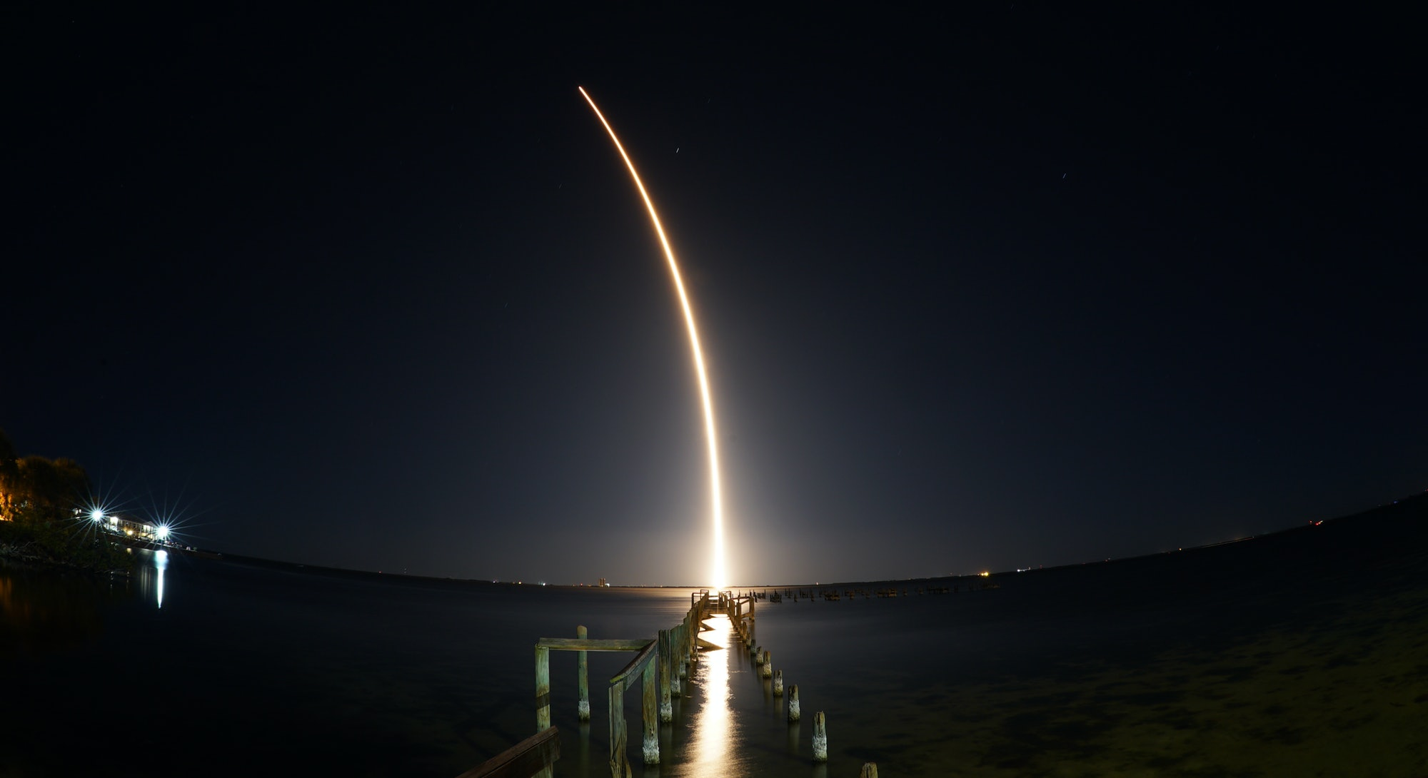 SpaceX rocket launch at night seen from Titusville, FL with destroyed dock in foreground