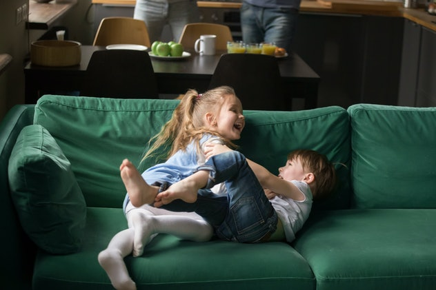 Happy cute little boy and girl playing together at home, preschool kids sister and brother laughing ...