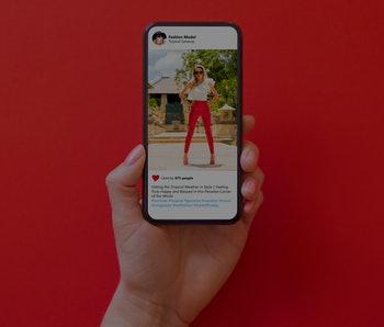 Woman holding phone in hand with photo of fashion model in red pants on red background
