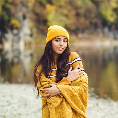 Young woman in yellow beanie standing in the forest during fall, affected by the October 2021 new mo...
