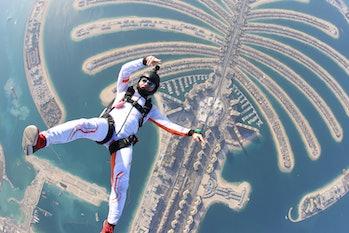 Dubai.People lies on beach Dubai Palm in free fall sky jump. Sea outdoor skydiving travel man. Free ...