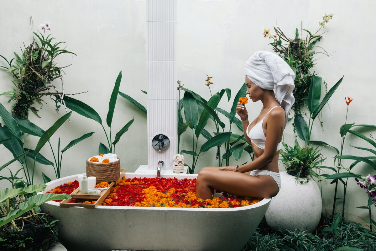 Woman with wrapped towel on head is relaxing in outdoor bath with flowers in Bali spa hotel.