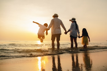 Happy asian family jumping together on the beach in holiday. Silhouette of the family holding hands ...