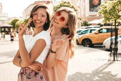 Two young beautiful smiling hipster girls in trendy summer clothes.Sexy carefree women posing on the...