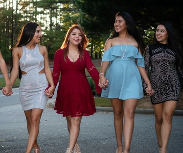 Sorority sisters walk hand in hand for a picture before their sorority formal, which they'll need In...