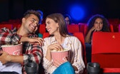 Couple with popcorn watching movie in cinema