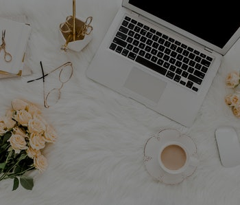 Female workspace with laptop, roses flowers bouquet, golden accessories, notebook, glasses. Flat lay...