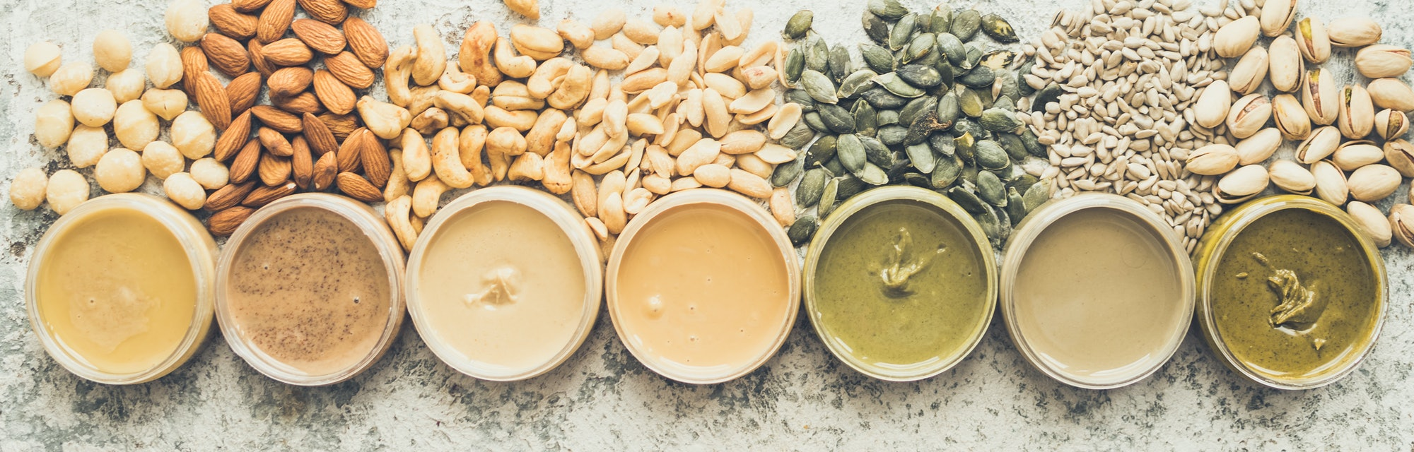 Nuts and seeds butter in jars with ingredients. Homemade raw organic peanut, almond, hazlenut, cashe...