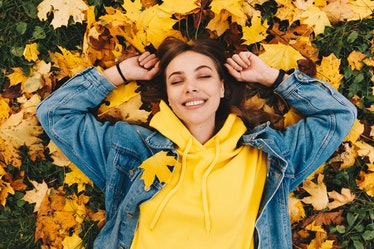 Young woman laying in leaves during fall, having the best week of October 18, 2021, per her zodiac s...
