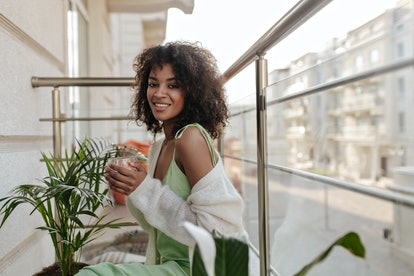 A woman smiles on an outdoor patio with plants around her, holding a beverage. Cusp signs in astrolo...