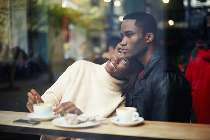 Portrait of young couple in love having coffee in a cafe and smiling.