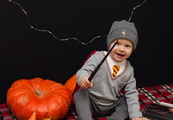 Little baby boy is reading a magic book in halloween time. Magic wand in a hand, black background an...