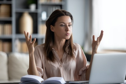 Unhappy young woman looking at laptop screen because she has a quincunx in astrology.
