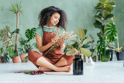 African american woman cultivating home plants, sitting on floor barefoot. Ispiring mixed race girl ...