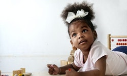 A Cute and adorable African girl lay down on the floor and drawing a picture with color pencil in th...
