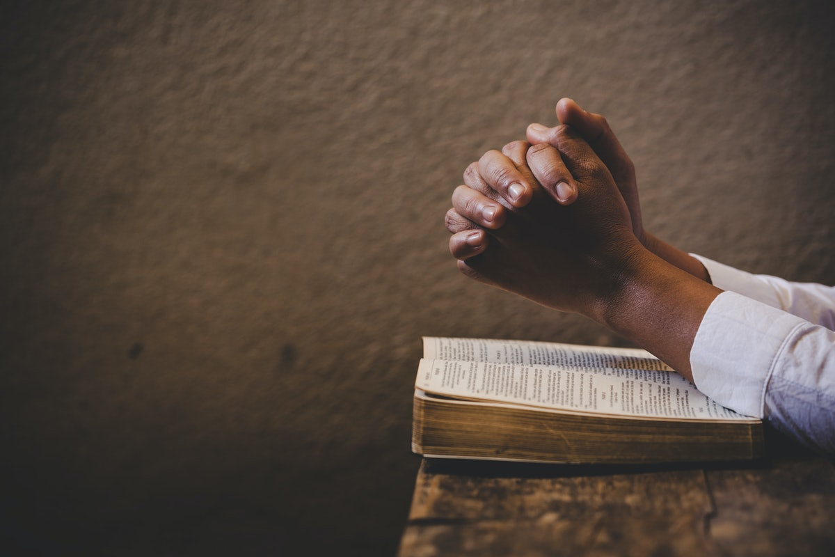 Hands folded in prayer on a Holy Bible in church concept for faith, spirituality and religion, woman...