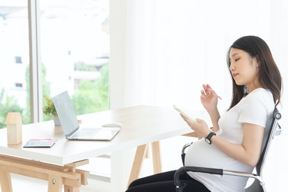 young pregnant woman working on computer at office