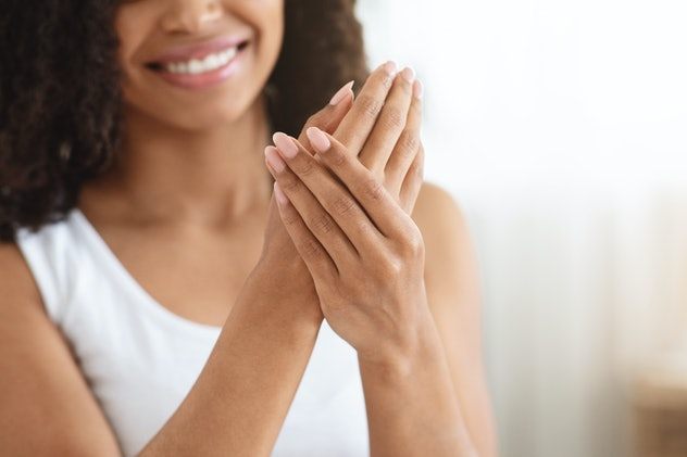 woman putting hand lotion on her hands