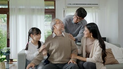 Asian elderly senior male grandpa sitting at sofa couch at home living room on quarantine in concept...