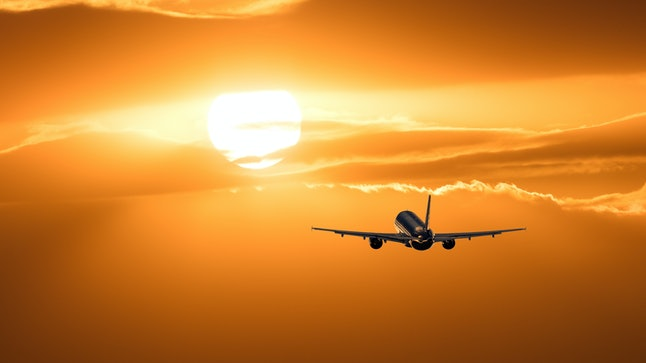 Plane is taking off at sunset.